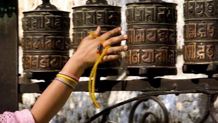 """""""A woman spins the prayer wheels at Swayambhunath Stupa in Kathmandu, Nepal."""""""