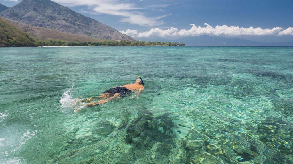 Man snorkeling in crystal blue waters, Komodo Islands, Indonesia