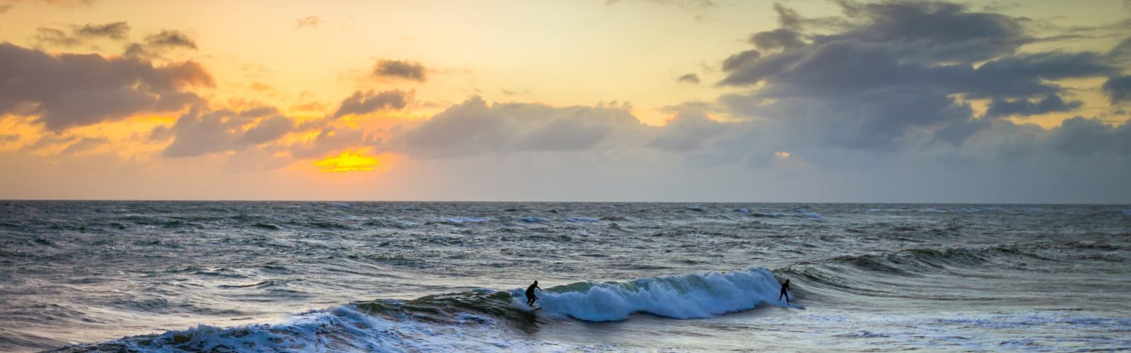 surfers-riding-waves-sunset
