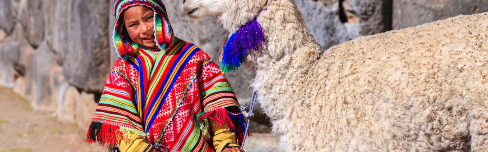 Peruvian little boy wearing national clothing with llama near Cuzco, Peru