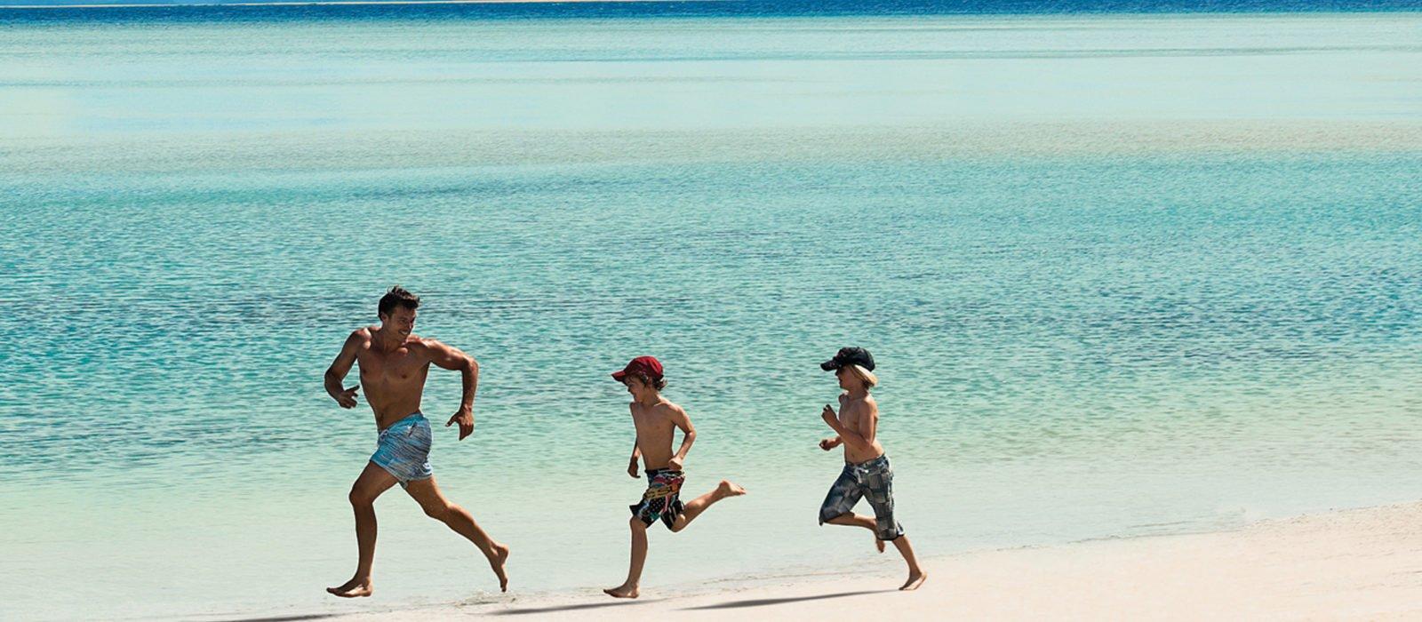 Family running along the beach, Hayman Island