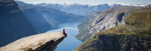 man sitting on trolltunga in norway