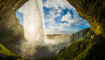 Waterfall tumbling into river above cavern mouth Seljalandsfoss Iceland
