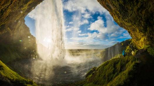 Waterfall tumbling into river above cavern mouth Seljalandsfoss Iceland