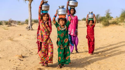 Young girls India, carrying water from well