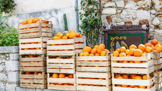 oranges in wooden boxes in street market, Italy