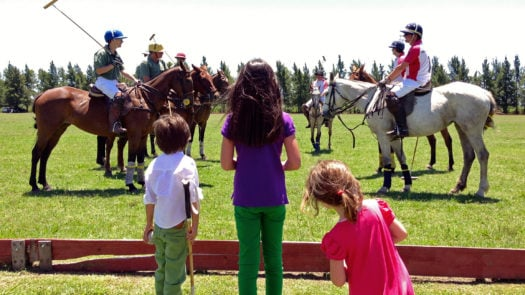 Three children watch a polo match, The Pampas, Argentina